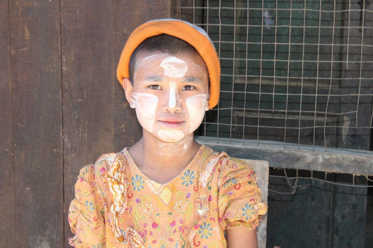 Um menino na frente da sua casa lendo um livro e usando thanaka, uma pasta cosmética branco-amarelada feita de casca de madeira usada frequentemente por locais.