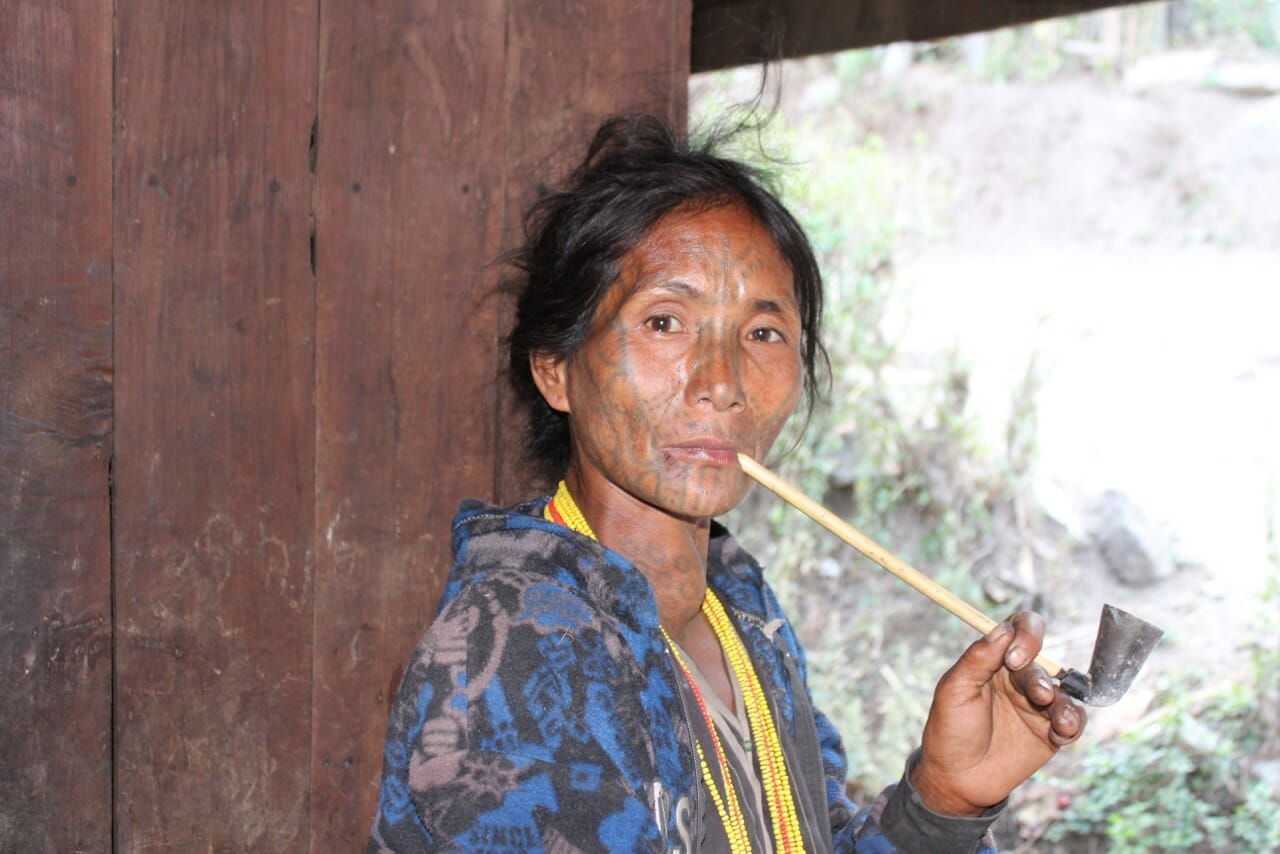 Uma das poucas mulheres com rosto tatuado em Myanmar fumando tabaco num cachimbo de bambu.