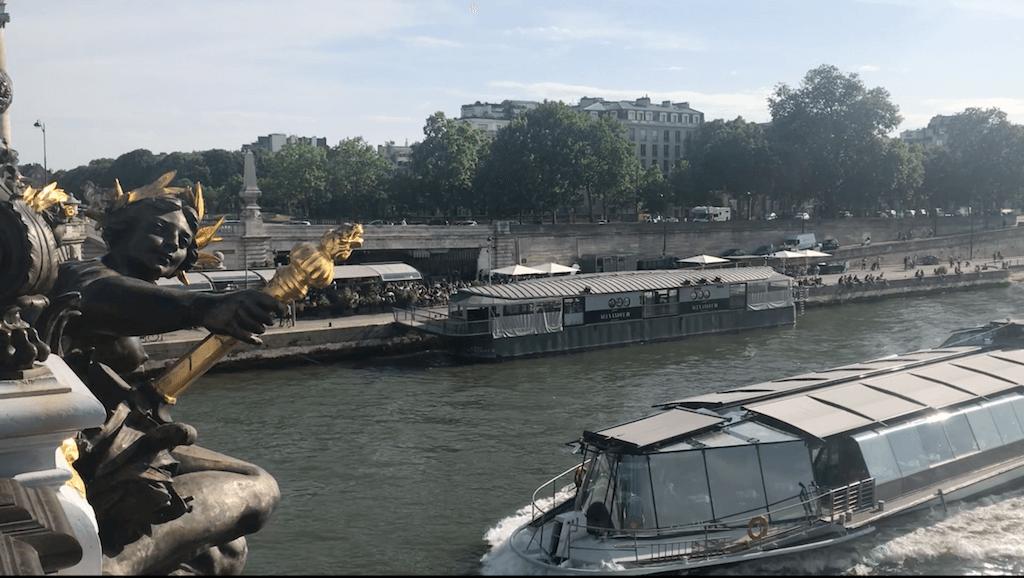 A bateaux bouche passing under the gorgeous bridge Pont Alexander III
